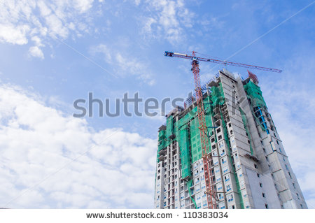 stock-photo-building-under-construction-with-crane-operating-and-blue-shy-background-110383034